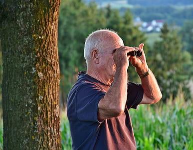 man wearing gray t-shirt near tree using black binoculars