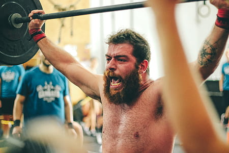 Man Carrying Black Barbell