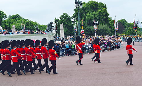 Royal Guards marching on gray concrete pavement surrounded with green trees during daytime