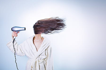 woman holding hair blower performing to dry her hair