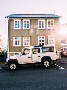 white Land Rover Defender SUV parked in front of brown 3-story building under gray clouds