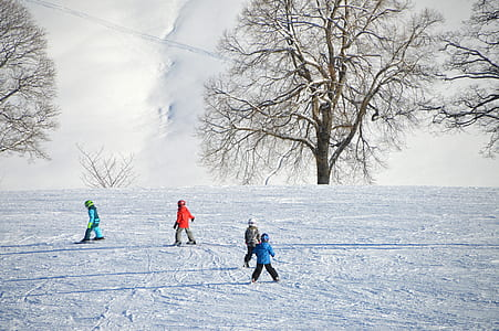 four children playing on snow at daytime