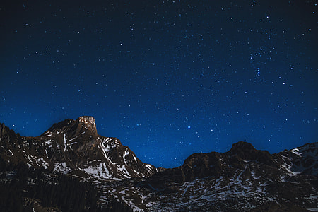 Snow-covered mountains at night with stars in sky