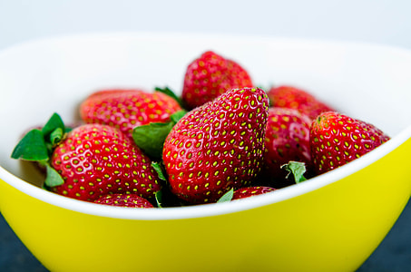 strawberry fruit in yellow bowl