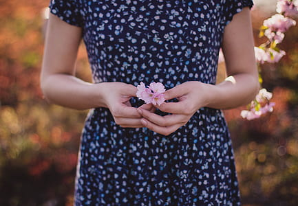 woman in blue short-sleeved dress holding pink flowers in shallow photograpy