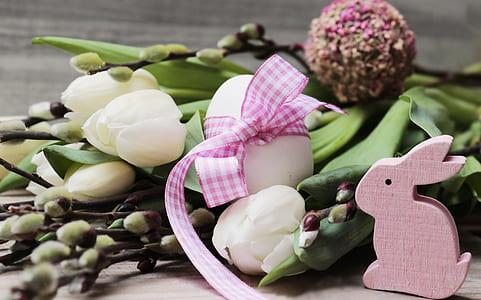 white petaled flowers beside pink rabbit figurine