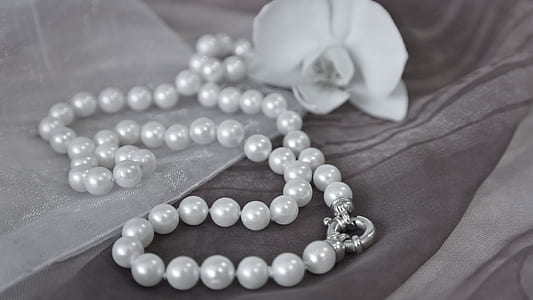 beaded white pearl necklace beside flower