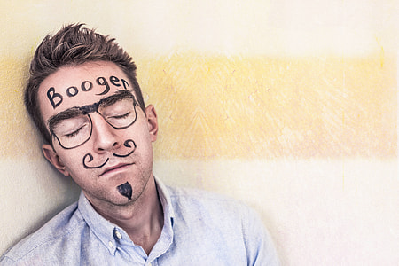 photo of sleeping man in light-blue button up collared top with booger print on his forehead print