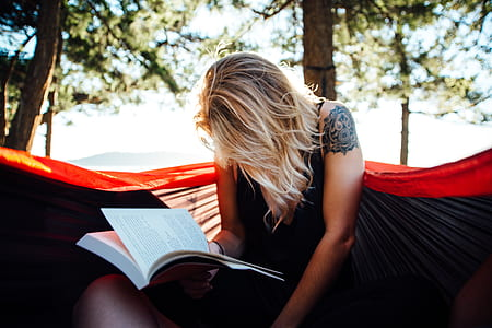 woman reading book on hammock at daytime