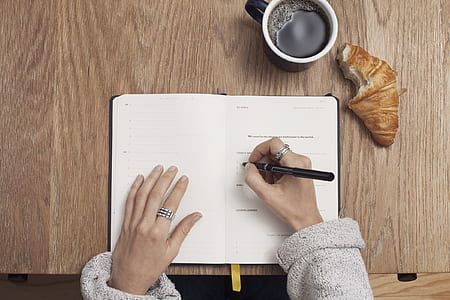 woman in sweater writing on her planner wallpaper