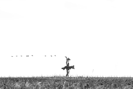 grayscale photography of woman in mini dress standing on grass