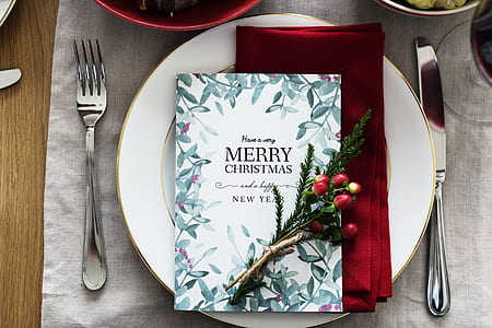 white porcelain plate with silverware on top of table with Christmas card