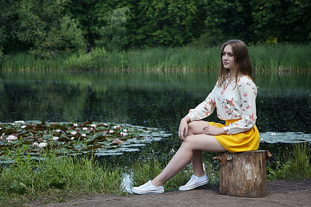 woman in white floral long-sleeved shirt and yellow mini skirt