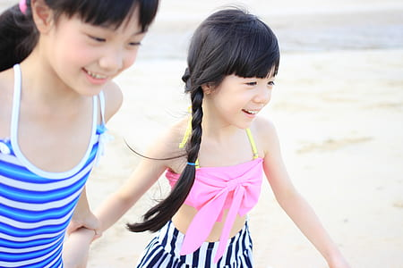 girl's in blue and pink spaghetti strap tops holding hands
