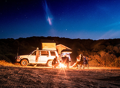 people camping beside white car during night time