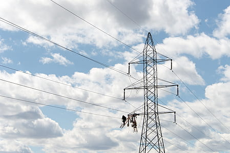 grey transmission line under white cloudy sky