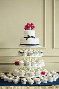 2-tier cake on top of round 4-tier cupcake rack with cupcakes