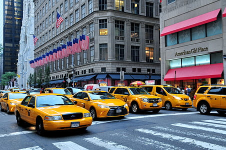 yellow cars on road near building with flag of America