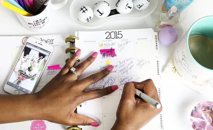 person writing calendar planner