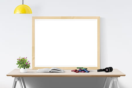 dry erase board with brown wooden frame on wooden table
