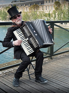 man playing accordion near body of water during daytime