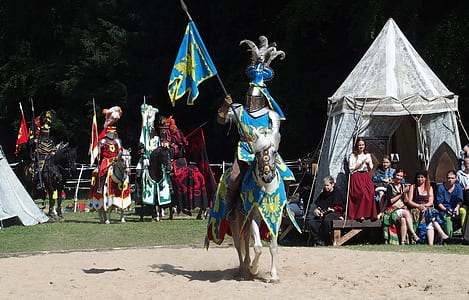 man in battle suit riding on horse during daytime