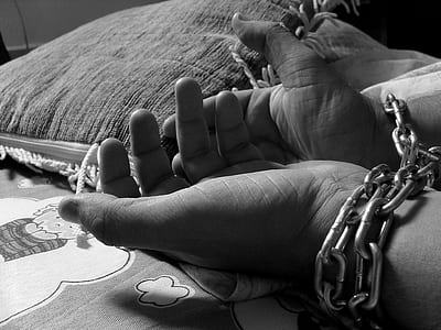 greyscale photo of human hands tied with grey chain