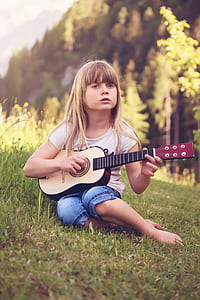girl in white t-shirt playing beige and brown guitar on grass field during daytime