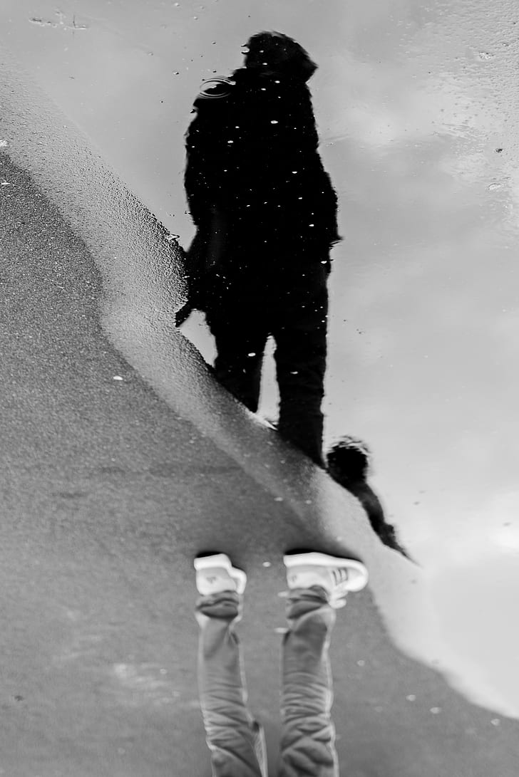Grayscale photo of man standing near water puddle