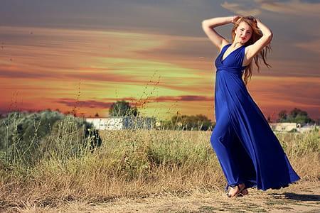 woman wearing blue jumpsuit standing near grass
