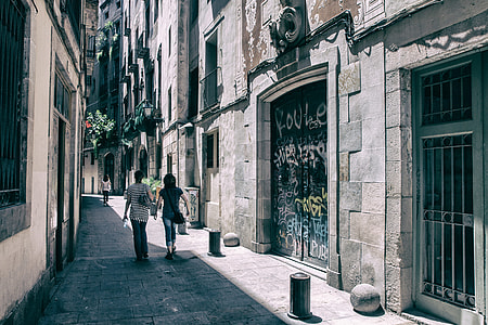 A couple of people walk through the streets of the Gothic Quarter in Barcelona, Spain