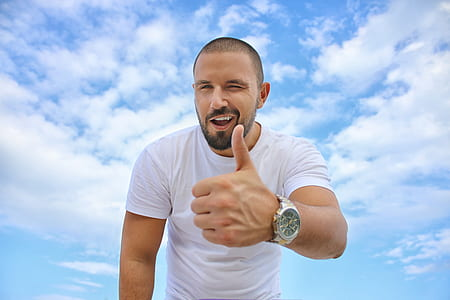 man wearing white shirt doing thumbs up under cumulus clouds