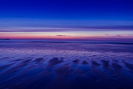 Beach at low-tide during a sunset at Watergate Bay in Cornwall, England