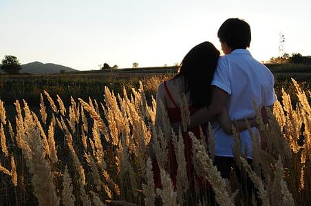 woman wearing red spaghetti strap top beside man wearing white dress shirt on green grass field photo
