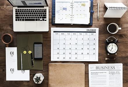 MacBook Pr, white calendar and brown folding on brown wooden desk