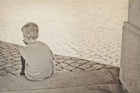 boy wearing gray top sitting on gray concrete surface