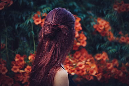 woman with red hair facing away towards red flowers