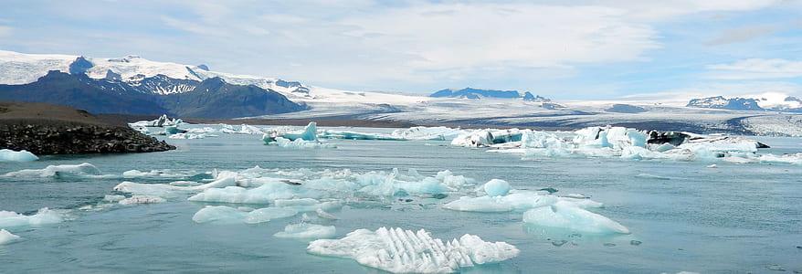 icebergs near mountains during daytime
