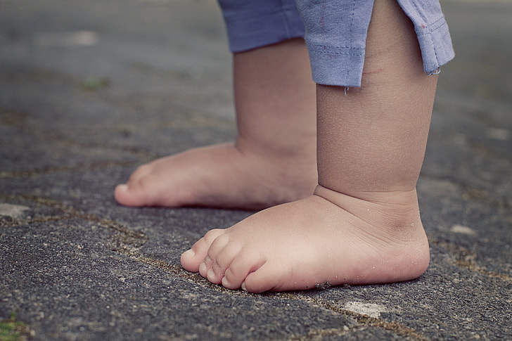 toddler standing with bare foot standing