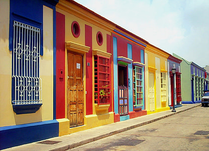 yellow, red, blue, and green 1-storey house under white clouds