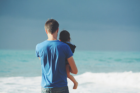 man in blue shirt carrying baby beside seashore