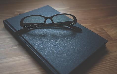 black framed eyeglasses with hardbound book