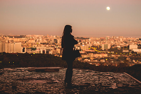 silhouette of woman near city during yellow sunset