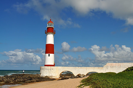red and white lighthouse near ocean
