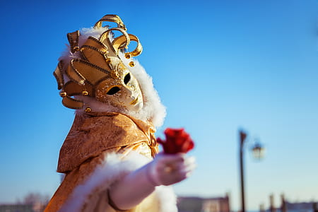 selective focus photography of person wearing white and gold mask