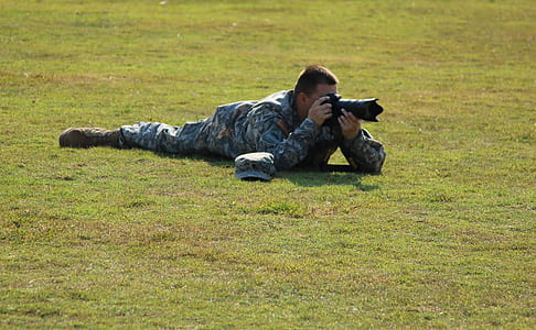 Military Crouching on Green Grass Using Dslr Camera during Daytime