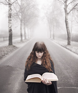 woman in black dress reading book on road during daytime