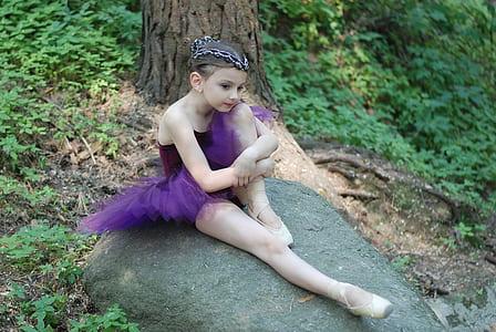 girl wearing purple tutu ballerina dress sits on gray rock