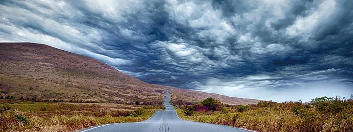 concrete road towards mountain under gray sky