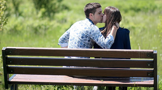 man in white and blue long-sleeved shirt sitting on bench near woman in black shirt while kissing